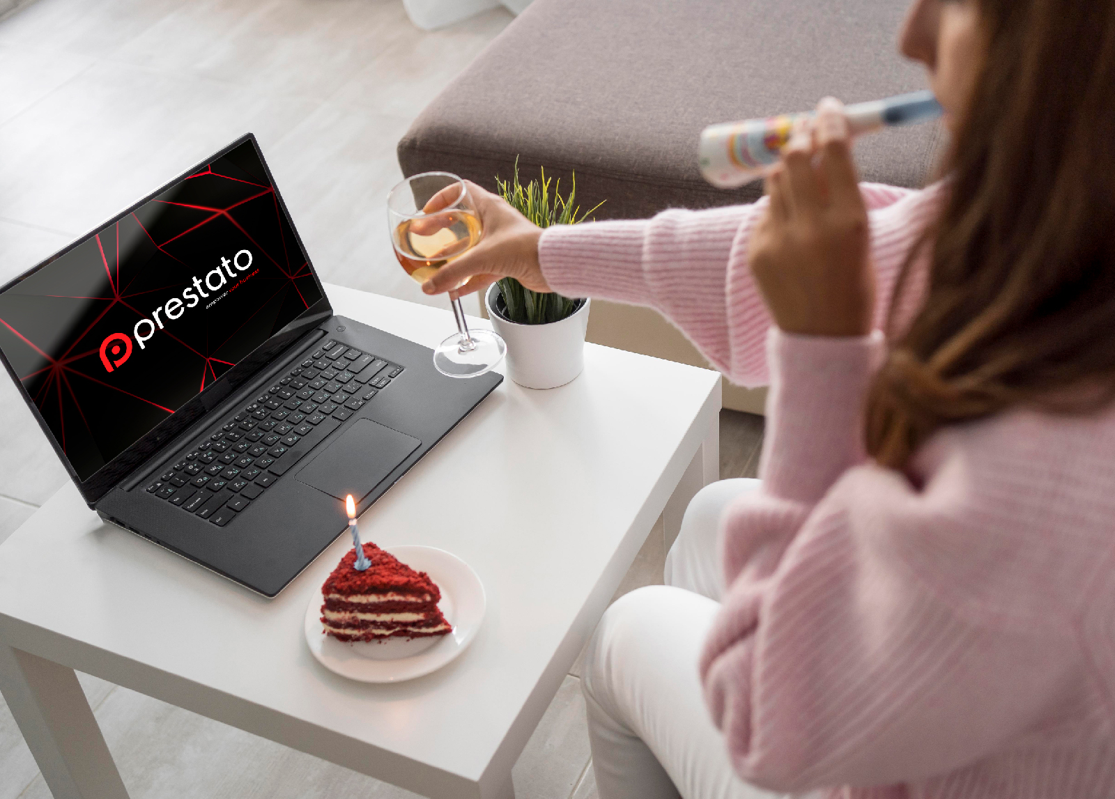 Woman celebrating with wine and cake, laptop with Prestato logo